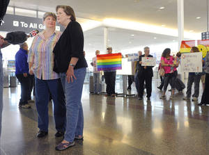 Photo -  Sharon Baldwin, left, and her partner Mary Bishop speak with members of the media before boarding a plane to Denver at Tulsa International Airport on Wednesday. Baldwin and Bishop plan to attend hearings at the 10th U.S. Circuit Court of Appeals in Denver on their lawsuit challenging Oklahoma's ban on gay marriage. ASSOCIATED PRESS  <strong>BRANDI SIMONS -   </strong>