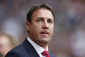 This is a  Saturday, Aug. 17, 2013 file photo of the then Cardiff City's manager Malky Mackay as he looks on from the dugout before the start of their English Premier League soccer match against West Ham United at Upton Park, London. The English Football Association siad Thursday Aug. 21, 2014 that it has opened an investigation after Cardiff submitted a dossier to the governing body about the conduct of former manager Malky Mackay and a member of his backroom staff. (AP Photo/Sang Tan/ File)