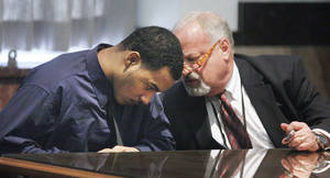 Photo - Rayvon Johnson, left, talks with his attorney, Mike Arnett, while sitting in the courtroom June 17 during the start of jury selection for his trial at the Oklahoma County courthouse. Photo by Paul B. Southerland, The Oklahoman <strong>PAUL B. SOUTHERLAND - PAUL B. SOUTHERLAND</strong>