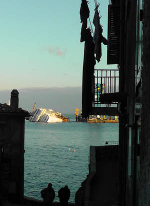 photo - The cruise ship Costa Concordia, leaning on its side, is seen from a street of the Tuscan island of Giglio, Italy, Saturday, Jan. 12, 2013. As if the nightmares, flashbacks and anxiety weren't enough, passengers who survived the terrifying grounding and capsizing of the Costa Concordia off Tuscany have come in for a rude shock as they mark the first anniversary of the disaster on Sunday. Ship owner Costa Crociere SpA, the Italian unit of Miami-based Carnival Corp., sent several passengers a letter telling them they weren't welcome at the official anniversary ceremonies on the island of Giglio where the hulking ship still rests. Costa says the day is focused on the families of the 32 people who died Jan. 13, 2012, not the 4,200 passengers and crew who survived. (AP Photo/Paolo Santalucia)