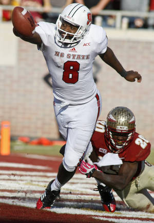 Photo - North Carolina State quarterback Brandon Mitchell (8) flips the ball for an incomplete pass to avoid a safety as Florida State defensive back Lamarcus Joyner (20) brings him down in the second quarter of an NCAA college football game on Saturday, Oct. 26, 2013, in Tallahassee, Fla. (AP Photo/Phil Sears)