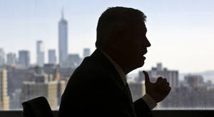 Photo - New York Jets coach Rex Ryan is silhouetted against the city skyline as he speaks during an interview on Friday, May 3, 2013 in New York.  (AP Photo/Bebeto Matthews)
