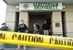 Photo -   U.S. marshals stand at the entrance of Oaksterdam University in Oakland, Calif., on Monday, April 2, 2012. The federal agents raided the medical marijuana training school at the heart of California's pot legalization movement. (AP Photo/Noah Berger)
