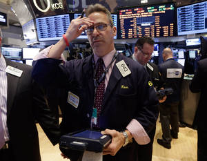 Photo - Trader Ronald Madarasz works on the floor of the New York Stock Exchange, Wednesday, Feb. 26, 2014.The stock market is little changed as investors pick over more earnings reports from retailers and other U.S. companies. (AP Photo/Richard Drew)