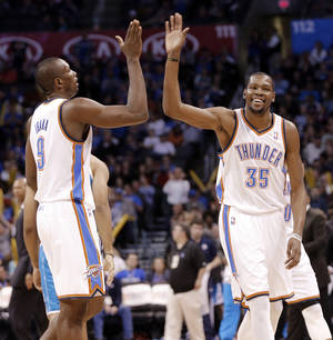 Photo - Oklahoma City Thunder's Kevin Durant (35) gives a high five to Serge Ibaka (9) during the NBA basketball game between the Oklahoma City Thunder and the New Orleans Hornets at the Chesapeake Energy Arena on Wednesday, Feb. 27, 2013, in Oklahoma City, Okla. Photo by Chris Landsberger, The Oklahoman
