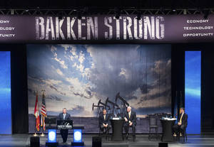 "Photo - The ""Bakken Strong"" theme was prevelant as Tommy Nusz, left, chairman and CEO of Oasis Petroleum; Harold Hamm, second from left, chairman of Continental Resources Inc., and and Jim Volker, chairman and CEO of Whiting Petroleum, speak Thursday, May 22, 2014, at the 22nd Williston Basin Petroleum Conference oil expo in Bismarck, N.D.. At right is Ron Ness, of the North Dakota Petroleum Council. (AP Photo/Kevin Cederstrom)"