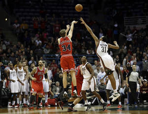 Photo - Chicago Bulls' Mike Dunleavy (34) puts up a game-winning three-point shot during the final seconds of an NBA basketball game against the Milwaukee Bucks, Friday, Dec. 13, 2013, in Milwaukee. The Bulls won 91-90. (AP Photo/Morry Gash)