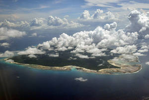 Photo - FILE – In this Nov. 14, 2005 file photo, clouds hang over the North Sentinel Island, in India's southeastern Andaman and Nicobar Islands. India used heat sensors on flights over hundreds of uninhabited Andaman Sea islands Friday, March 14, 2014, and will expand its search for the missing Malaysia Airlines jet farther west into the Bay of Bengal, officials said. The Indian-controlled archipelago that stretches south of Myanmar contains 572 islands covering an area of 720-by-52 kilometers. Only 37 are inhabited, with the rest covered in dense forests. (AP Photo/Gautam Singh, File)