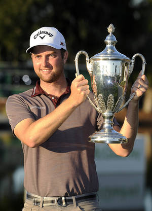 Photo - Chris Kirk holds the trophy after winning the final round of the McGladrey Classic golf tournament on Sunday, Nov. 10, 2013, in St. Simons Island, Ga. (AP Photo/Stephen Morton)