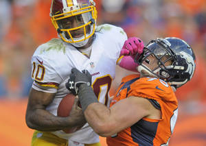 Photo - Washington Redskins quarterback Robert Griffin III (10) stiff arms Denver Broncos defensive end Derek Wolfe (95) in the fourth quarter of an NFL football game, Sunday, Oct. 27, 2013, in Denver. (AP Photo/Jack Dempsey)