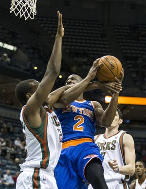 Photo - Milwaukee Bucks' Khris Middleton tries to stop New York Knicks' Raymond Felton from shooting the ball during the first half of an NBA basketball game, Monday, Feb. 3, 2014, in Milwaukee. (AP Photo/Tom Lynn)