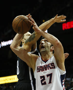 Photo - Atlanta Hawks center Zaza Pachulia (27) is fouled by Brooklyn Nets point guard Deron Williams (8) in the first half of an NBA basketball game on Wednesday, Jan. 16, 2013, in Atlanta. (AP Photo/John Bazemore)