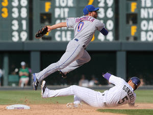 Photo - New York Mets shortstop Omar Quintanilla, top, jumps over Colorado Rockies' Carlos Gonzalez after forcing Gonzalez out at second base on the front end of a double play hit into by Nolan Arenado to end the eighth inning of the Mets' 5-1 victory in a baseball game in Denver, Sunday, May 4, 2014. (AP Photo/David Zalubowski)