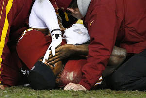 photo - Washington Redskins quaterback Robert Griffin III lies on the ground after fumbling the ball against the Seattle Seahawks during the fourth quarter of an NFL football wild card playoff game Sunday, Jan. 6, 2013, in Landover, Md. Griffin left the game. (AP Photo/The Seattle Times, John Lok) SEATTLE OUT  MAGS OUT  NO SALES  MANDATORY CREDIT  TV OUT  USA TODAY OUT