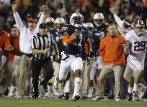 Photo - Auburn cornerback Chris Davis (11) returns a missed field goal attempt 100-plus yards to score the game-winning touchdown as time expired in the fourth quarter of an NCAA college football game against Alabama in Auburn, Ala., Saturday, Nov. 30, 2013. Alabama kicker Cade Foster was inundated with support from teammates and thousands of fans on social media after missing two field goal attempts and having a third blocked Saturday. (AP Photo/Dave Martin)
