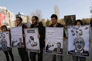 "Photo - Members of the Turkish Youth Union hold cartoons depicting Turkey's Prime Minister Recep Tayyip Erdogan during a protest against a ban on Twitter, in Ankara, Turkey, Friday, March 21, 2014. Turkey's attempt to block access to Twitter appeared to backfire on Friday with many tech-savvy users circumventing the ban and suspicions growing that the prime minister was using court orders to suppress corruption allegations against him and his government. Cartoon second right reads: Erdogan, left, to his Ankara Mayor Melih Gokcek "" we will rip out the roots of Twitter."" Gokcek: ""don't say it.""(AP Photo/Burhan Ozbilici)"