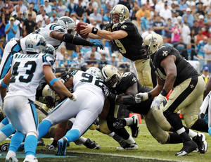 Photo -   New Orleans Saints' Drew Brees (9) reaches the ball over the goal line for a touchdown against the Carolina Panthers during the fourth quarter of an NFL football game in Charlotte, N.C., Sunday, Sept. 16, 2012. The Panthers won 35-27. (AP Photo/Bob Leverone)
