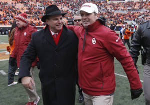Photo - Oklahoma head coach Bob Stoops, right walks off the field with athletic director Joe Castiglione, left, following a victory over Oklahoma State in an NCAA college football game in Stillwater, Okla., Saturday, Dec. 7, 2013. Oklahoma won 33-24. (AP Photo/Sue Ogrocki)