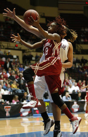 photo - OU's Danielle Robinson (13) leaps past Texas A&M's Danielle Adams (23) to the basket during the women's college basketball Big 12 Championship tournament game between the University of Oklahoma and Texas A&M in Kansas City, Mo., Friday, March 11, 2011.  Photo by Bryan Terry, The Oklahoman