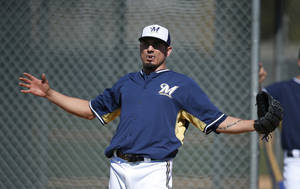 Photo - Milwaukee Brewers' Matt Garza stretches out as he adjusts his mouth guard between throwing pitches during Brewers spring training baseball practice, Monday, Feb. 17, 2014, in Phoenix. (AP Photo/Ross D. Franklin)