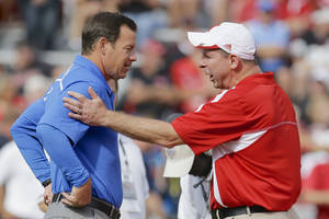 Photo - UCLA head coach Jim Mora, left, and Nebraska head coach Bo Pelini meet during warmups prior to an NCAA college football game in Lincoln, Neb., Saturday, Sept. 14, 2013. (AP Photo/Nati Harnik)