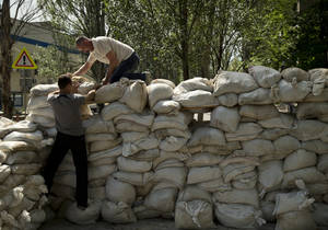 Photo - People pile up sand bags to set up a shooting position on the road leading from the airport to Donetsk, Ukraine, Tuesday, May 27, 2014. The eastern city of Donetsk was in turmoil Tuesday a day after government forces used fighter jets to stop pro-Russia separatists from taking over the airport. The mayor said 40 people were killed and went on television to urge residents to stay at home.(AP Photo/Vadim Ghirda)