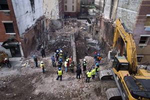 Photo - FILE - In this Sunday, March 16, 2014, file photo, workers stand beside the recently cleared basements of two buildings leveled by an explosion last week in the East Harlem neighborhood of New York. A gas main leak has been found at the site of the explosion that killed eight people and leveled two Manhattan buildings, federal investigators said Tuesday, March 18, 2014, but cautioned that they're still a long way from determining what caused the blast. (AP Photo/John Minchillo, File)