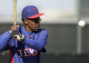 Photo - Texas Rangers manager Ron Washington prepares to hit a ball as he works out infielders during spring training baseball practice, Sunday, Feb. 23, 2014, in Surprise, Ariz. (AP Photo/Tony Gutierrez)