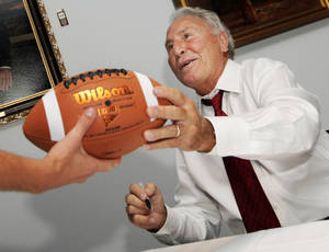 Photo - ESPN college football analyst Lee Corso returns a football to a fan after autographing during the St. Anthony Stroke of Courage event at the Gaylord-Pickens Oklahoma Heritage Museum. Corso spoke earlier about being a stroke survivor. Photo by Nate Billings, The Oklahoman