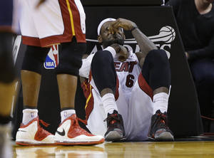 Photo - Miami Heat's LeBron James sits on the court after being elbowed by Charlotte Bobcats' Josh McRoberts during the second half in Game 2 of an opening-round NBA basketball playoff series, Wednesday, April 23, 2014, in Miami. The Heat defeated the Bobcats 101-97. (AP Photo/Lynne Sladky)