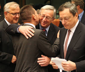 "Photo -   Luxembourg's Prime Minister and chairman of the Eurogroup Jean-Claude Juncker, second right, greets Greek Finance Minister Yannis Stournaras, second left, as European Commissioner for Economic and Monetary Affairs Olli Rehn, left, and President of the European Central Bank Mario Draghi, right, look on, during the Eurogroup finance ministers meeting in Brussels, Monday, Nov, 12, 2012. Greece's international lenders have prepared a ""positive"" report on the country's reform efforts, a crucial step in its efforts to secure the next installment of its bailout loan, the head the of group of finance ministers from the 17 euro countries said Monday. (AP Photo/Yves Logghe)"