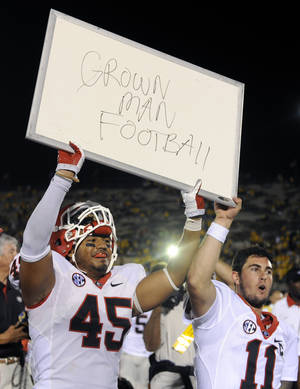 Photo - Georgia's Christian Robinson, left, and teammate Aaron Murray hold up a sign following Georgia's 41-20 victory over Missouri in the Tigers' first SEC game in Columbia, Mo. AP PHOTO