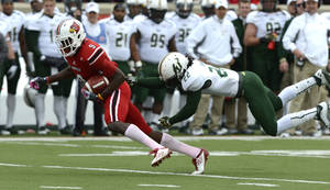 Photo -   Louisville's DeVante Parker, left, outruns the grasp of South Florida's George Baker during action of their NCAA colege football game Saturday Oct. 20, 2012 in Louisville, Ky. Louisville defeated USF 27-25. (AP Photo/Timothy D. Easley)