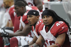 Photo -   Arizona Cardinals cornerback Justin Bethel (31) and Rashad Johnson (49) watch the scoreboard in the second half of an NFL football game against the Minnesota Vikings in Minneapolis, Sunday, Oct. 21, 2012. The Vikings won 21-14. (AP Photo/Jim Mone)
