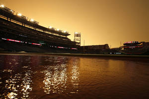 Photo - The orange sky is reflected in a puddle during a rain delayed start of an interleague baseball game between the Washington Nationals and the Baltimore Orioles at Nationals Park, Tuesday, July 8, 2014, in Washington. (AP Photo/Alex Brandon)