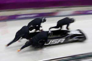 Photo - The team from the United States USA-1, piloted by Steven Holcomb, start a run during the men's four-man bobsled training at the 2014 Winter Olympics, Friday, Feb. 21, 2014, in Krasnaya Polyana, Russia. (AP Photo/Dita Alangkara)