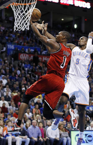 Photo - Miami Heat center Chris Bosh (1) shoots in front of Oklahoma City Thunder forward Serge Ibaka (9) in the first quarter of an NBA basketball game in Oklahoma City, Thursday, Feb. 14, 2013. (AP Photo/Sue Ogrocki)