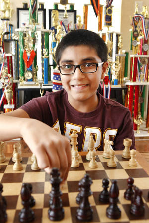 Photo -  Chess whiz Advait Patel, 11, who is ranked no. 2 in the country for his age group, sits in front of his trophies. Photo by David McDaniel, The Oklahoman  <strong>David McDaniel -   </strong>