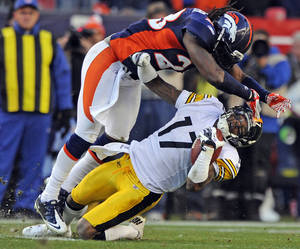 Photo - Denver Broncos safety Quinton Carter, top, hits Pittsburgh Steelers wide receiver Mike Wallace during the second quarter of an NFL wild card playoff football game, Sunday, Jan. 8, 2012, in Denver. (AP Photo/The Denver Post, AAron Ontiveroz)  MANDATORY CREDIT; MAGS OUT; TV OUT ORG XMIT: CODEN201