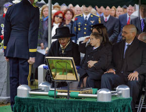 Photo - Max Karmazyn, center, sitting next to his grandmother Brenda Schwarzkopf, left, salutes during the burial of his late grandfather, Gen. Norman Schwarzkopf,  at the United States Military Academy on Thursday, Feb. 28, 2013, in West Point, N.Y. Schwarzkopf was 78 when he died of complications from pneumonia on Dec. 27 in Tampa. (AP Photo/Philip Kamrass)