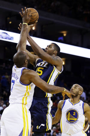 Photo - Utah Jazz's Derrick Favors (15) shoots over Golden State Warriors' Carl Landry during the first half of an NBA basketball game, Sunday, April 7, 2013, in Oakland, Calif. (AP Photo/Ben Margot)