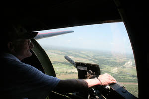 Photo - Veteran Joe Jones surveys Norman as he looks out the window of one of the .50-caliber waist machinegun positions during his ride on a World War II-era B-17 Flying Fortress bomber. Photo provided <strong></strong>