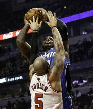 Photo -   Chicago Bulls' Carlos Boozer (5) tries to block a shot by Orlando Magic's Glen Davis during an NBA basketball game in Chicago on Tuesday, Nov. 6, 2012. (AP Photo/Charles Cherney)
