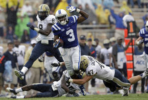 Photo - Duke's Jamison Crowder (3) runs the ball as Pittsburgh's Matt Galambos (47) dives for the tackle during the second half of an NCAA college football game in Durham, N.C., Saturday, Sept. 21, 2013. Pittsburgh won 58-55. (AP Photo/Gerry Broome)
