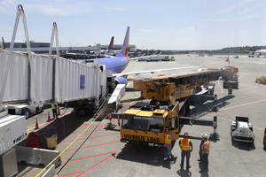 Photo - A large crane stands ready to lift a jetway, right, that had a mechanical failure and slowly lowered to the ground Tuesday, May 13, 2014, while connected to a Southwest Airlines airplane at Seattle-Tacoma International Airport. The incident happened as passengers from Phoenix were deplaning. The next leg of the flight to Chicago had to be canceled so the jetway could be removed from the airplane and a damage inspection could be completed. (AP Photo)