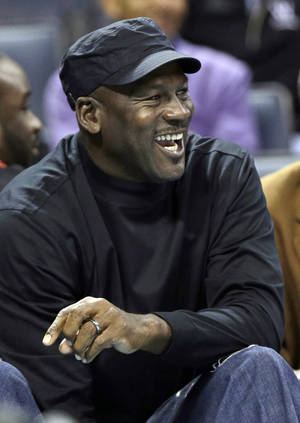 Photo - Charlotte Bobcats owner Michael Jordan sits during the first half of an NBA basketball game against the Brooklyn Nets in Charlotte, N.C., Wednesday, Nov. 20, 2013. (AP Photo/Chuck Burton)