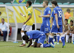 Photo - Italy forward Mario Balotelli (9) grimaces during the Confederations Cup group A soccer match between Italy and Brazil at Fonte Nova stadium in Salvador, Brazil, Saturday, June 22, 2013. Balotelli will miss Italy's semifinal game against Spain on Thursday due to a strained thigh. (AP Photo/Antonio Calanni)