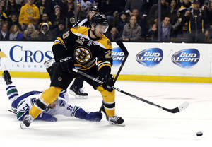 Photo - Boston Bruins left wing Daniel Paille (20) shoots and scores on a breakaway as Vancouver Canucks defenseman Frank Corrado (26) tries to stop him during the second period of an NHL hockey game in Boston on Tuesday, Feb. 4, 2014. (AP Photo/Elise Amendola)