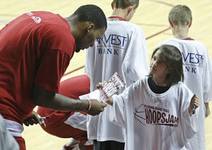 "photo - Taryn Phillips, right, age seven, of Blanchard, Okla., asks Oklahoma's Romero Osby, left, for an autograph, following an open ""Hoops Jam"" NCAA college basketball practice in Norman, Okla., Sunday, Oct. 16, 2011. Oklahoma men's basketball fans got their first look at the 2011-12 Sooners on the hardwood at its ""Hoops Jam 2011"" event. (AP Photo/Sue Ogrocki) ORG XMIT: OKSO104"