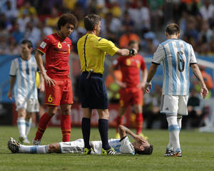 Photo - Argentina's Angel di Maria lies on the ground injured as referee Nicola Rizzoli from Italy requests a stretcher to take him off the pitch during the World Cup quarterfinal soccer match between Argentina and Belgium at the Estadio Nacional in Brasilia, Brazil, Saturday, July 5, 2014. At left is Belgium's Axel Witsel and at right, Argentina's Lucas Biglia.(AP Photo/Eraldo Peres)